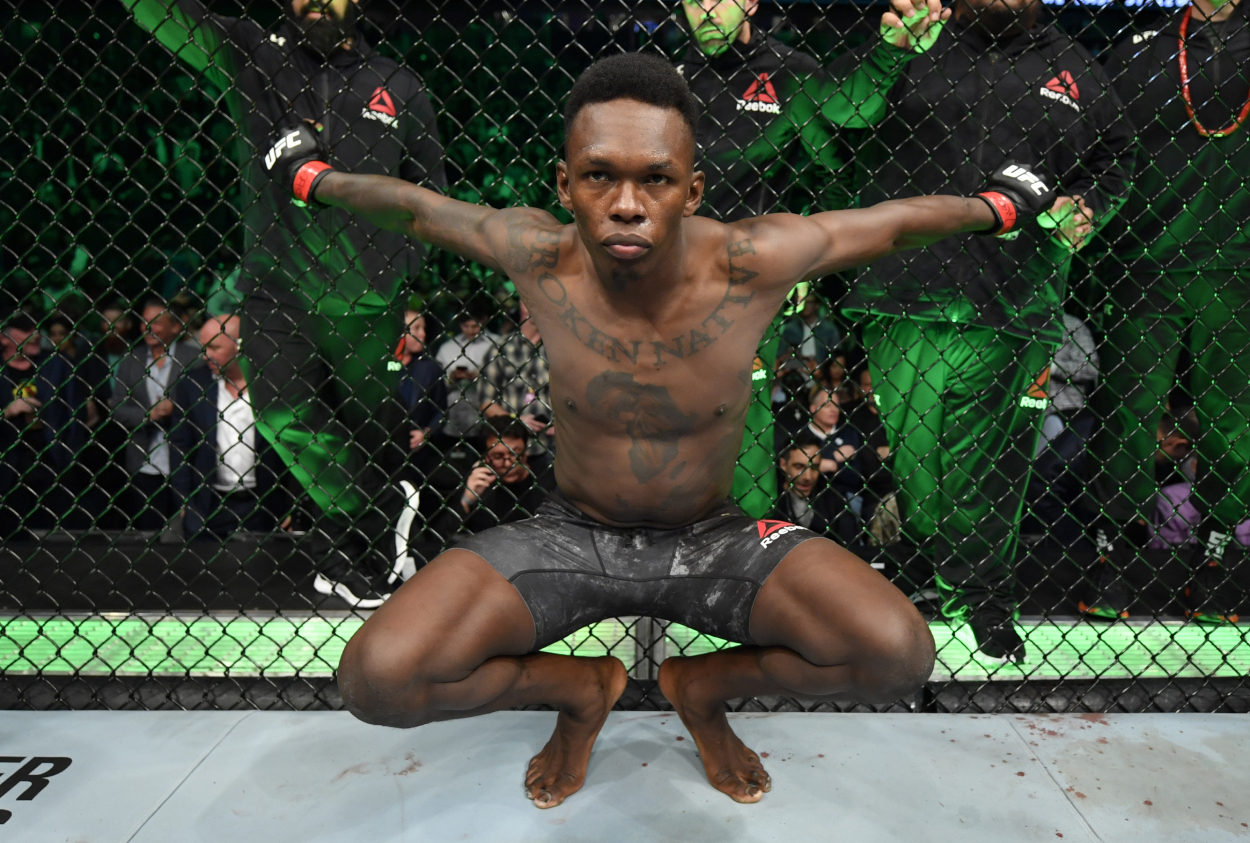 Israel Adesanya grabbing the cage before a UFC fight