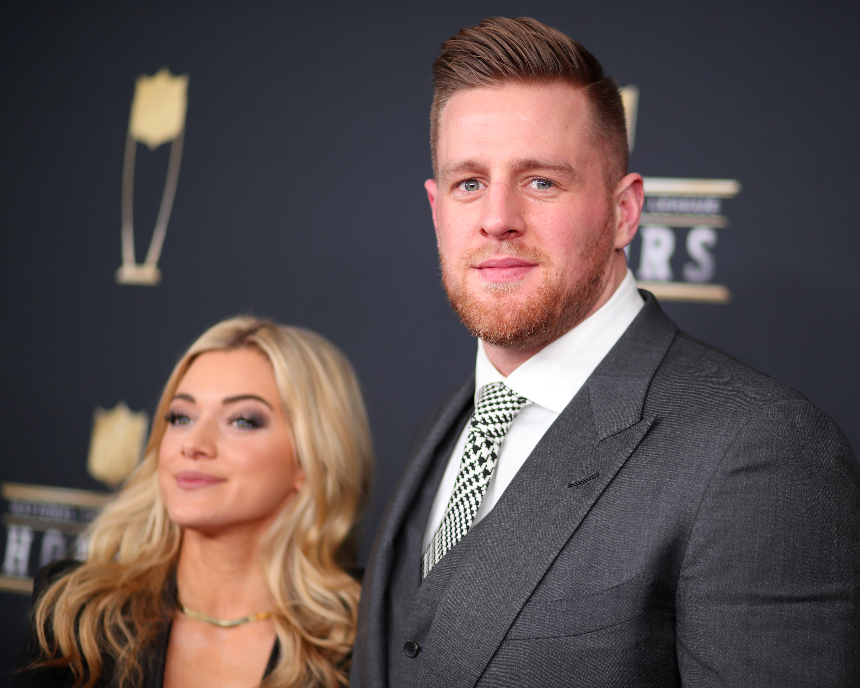 JJ Watt and his wife Kealia Ohai smile for a photo on the red carpet