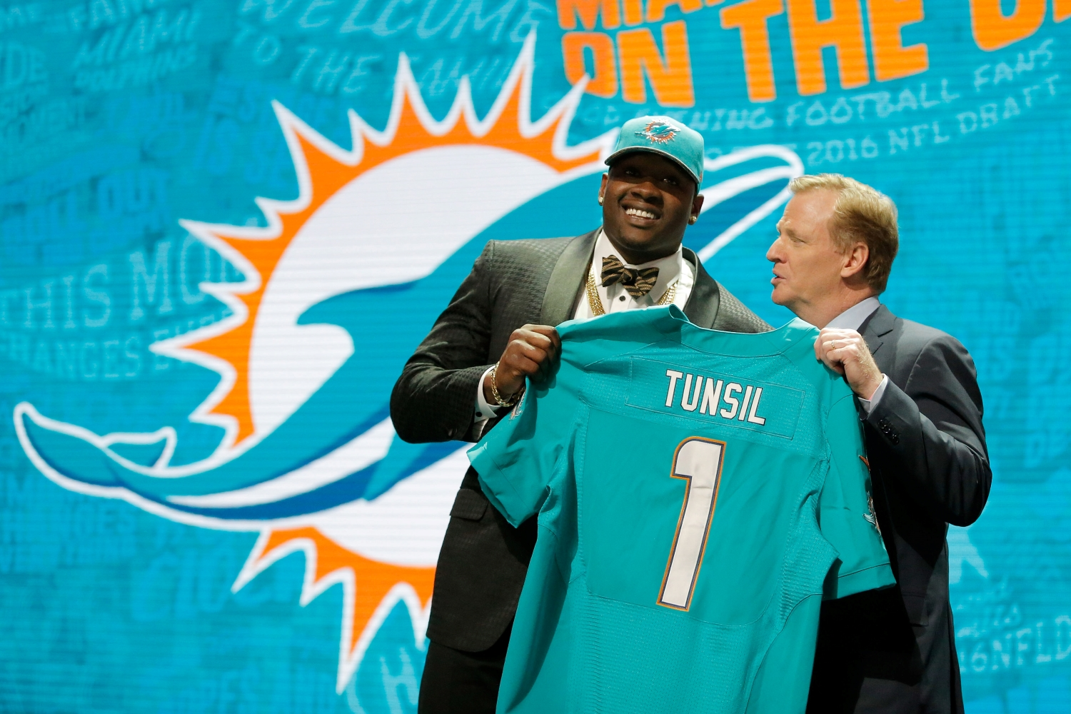 Laremy Tunsil holds up his Dolphins jersey with Roger Goodell after he got selected in the first round of the 2016 NFL draft.