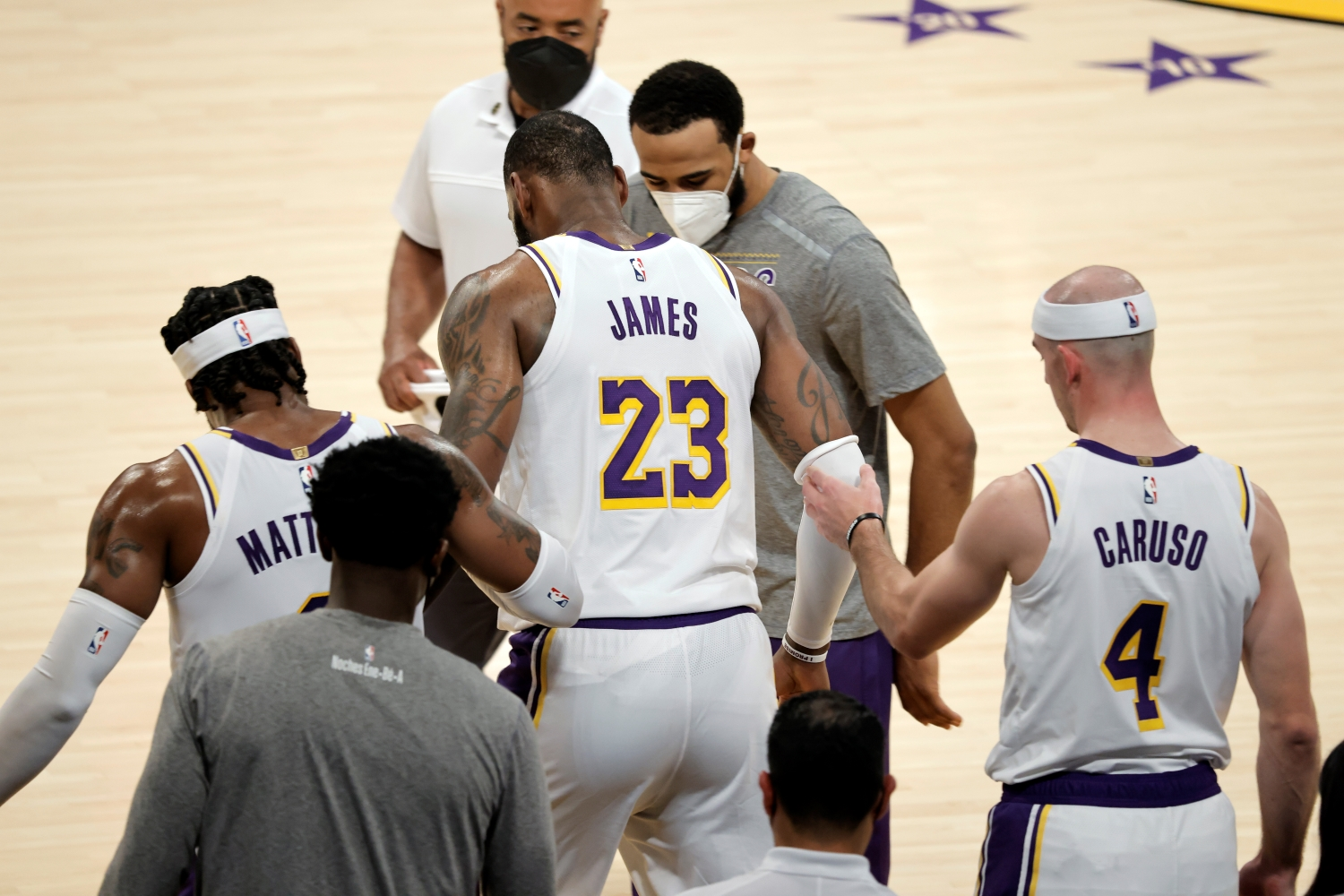 LeBron James receives help from his Lakers teammates after suffering an injury against the Atlanta Hawks on March 20, 2021.