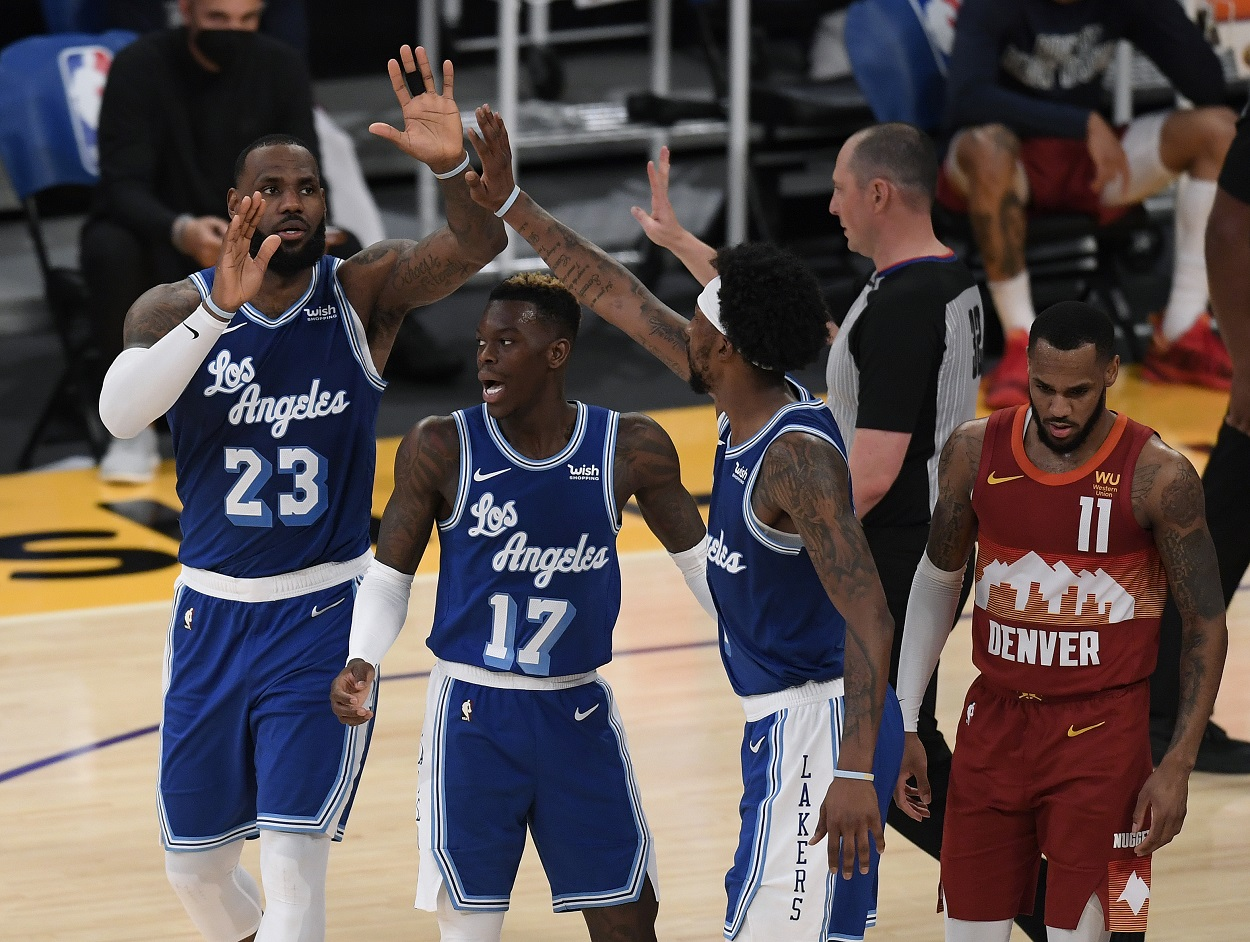 Lakers' players LeBron James, Dennis Schroder, and Kentavious Caldwell-Pope give each other high fives are a play against the Denver Nuggets.