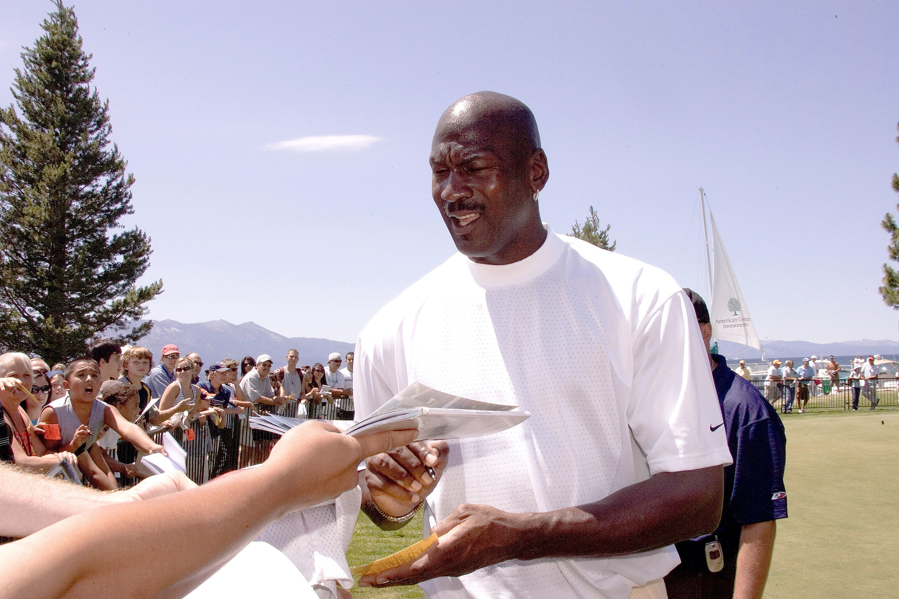 Chicago Bulls legend Michael Jordan signs an autograph on the golf course.