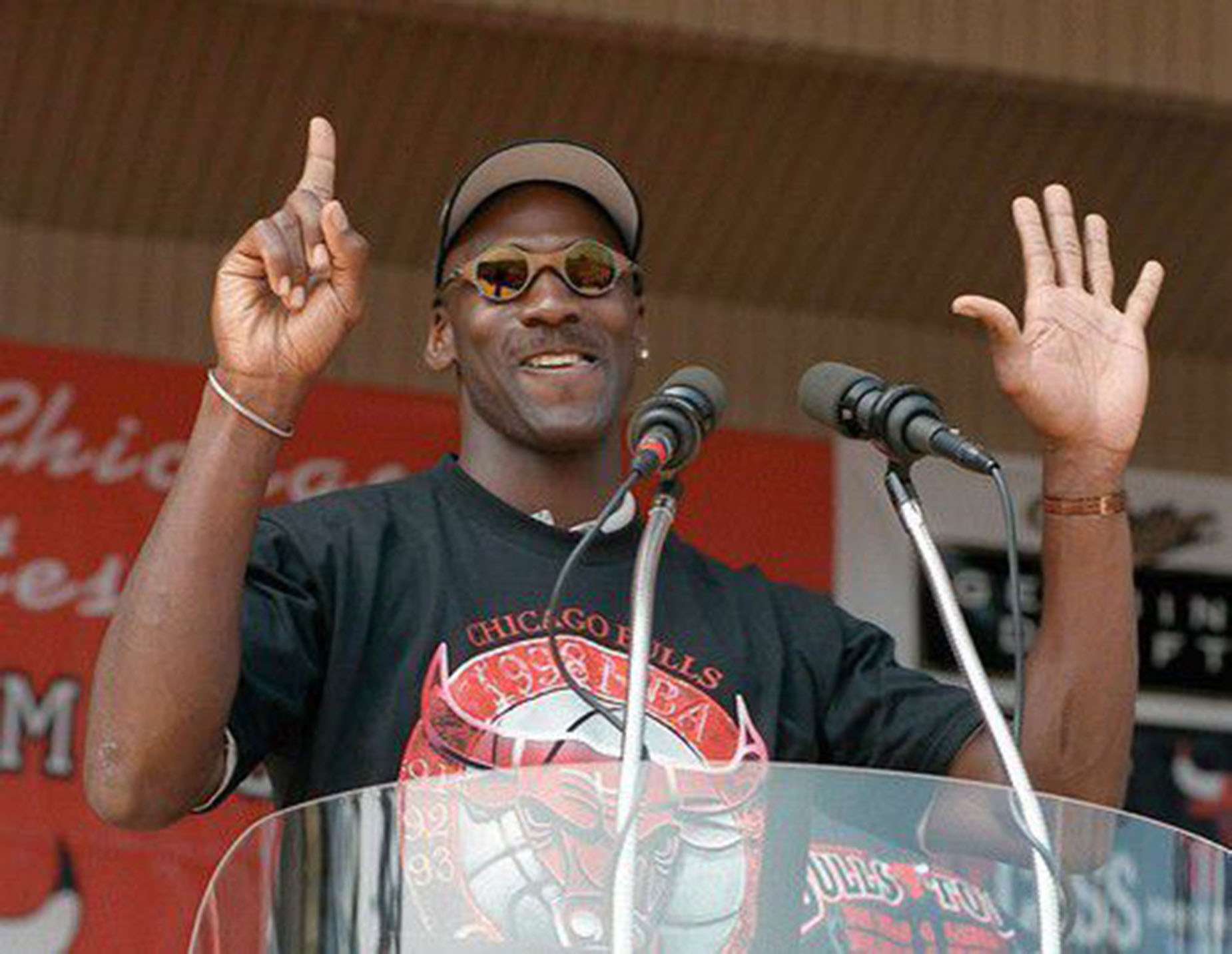 Michael Jordan holds up six fingers at a rally celebrating the Chicago Bulls sixth NBA championship.