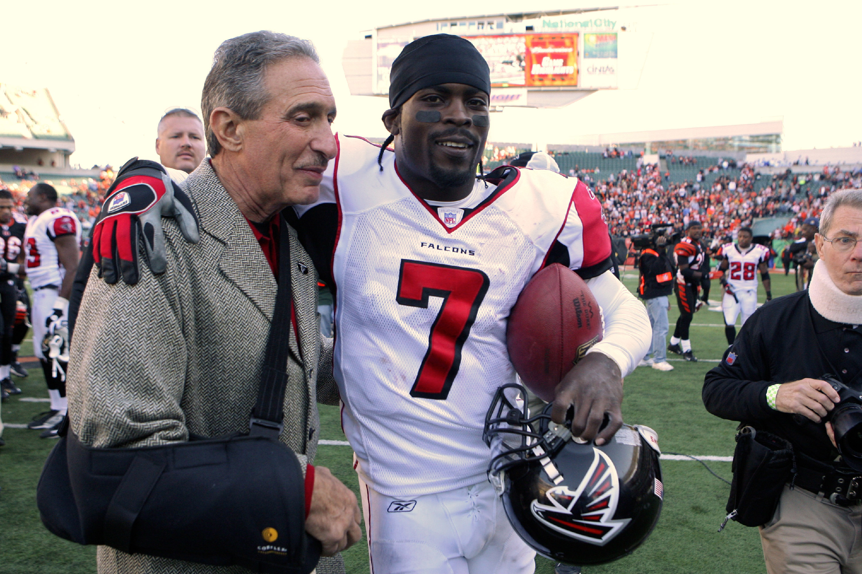 Atlanta Falcons owner Arthur Blank hugs his quarterback Mike Vick