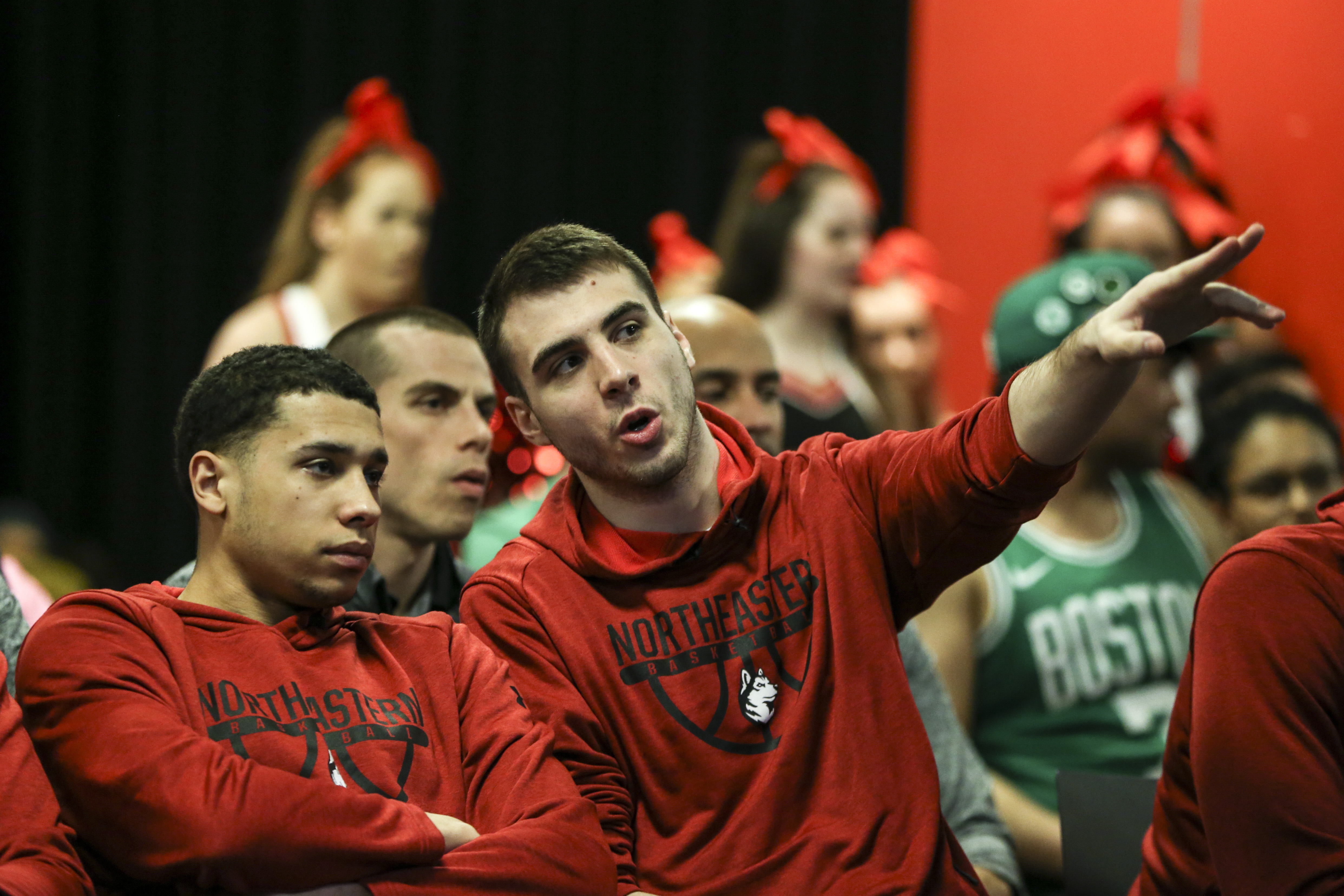 Northeastern University basketball guard Vasa Pusica (R) points to the TV during an NCAA Tournament Selection Sunday watch party in 2019