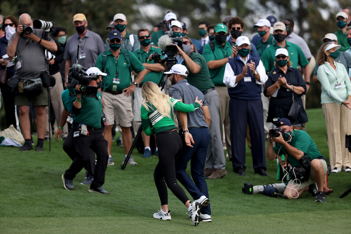 Dustin Johnson walks off the green with fiancée Paulina Gretzky after winning the 2020 Masters