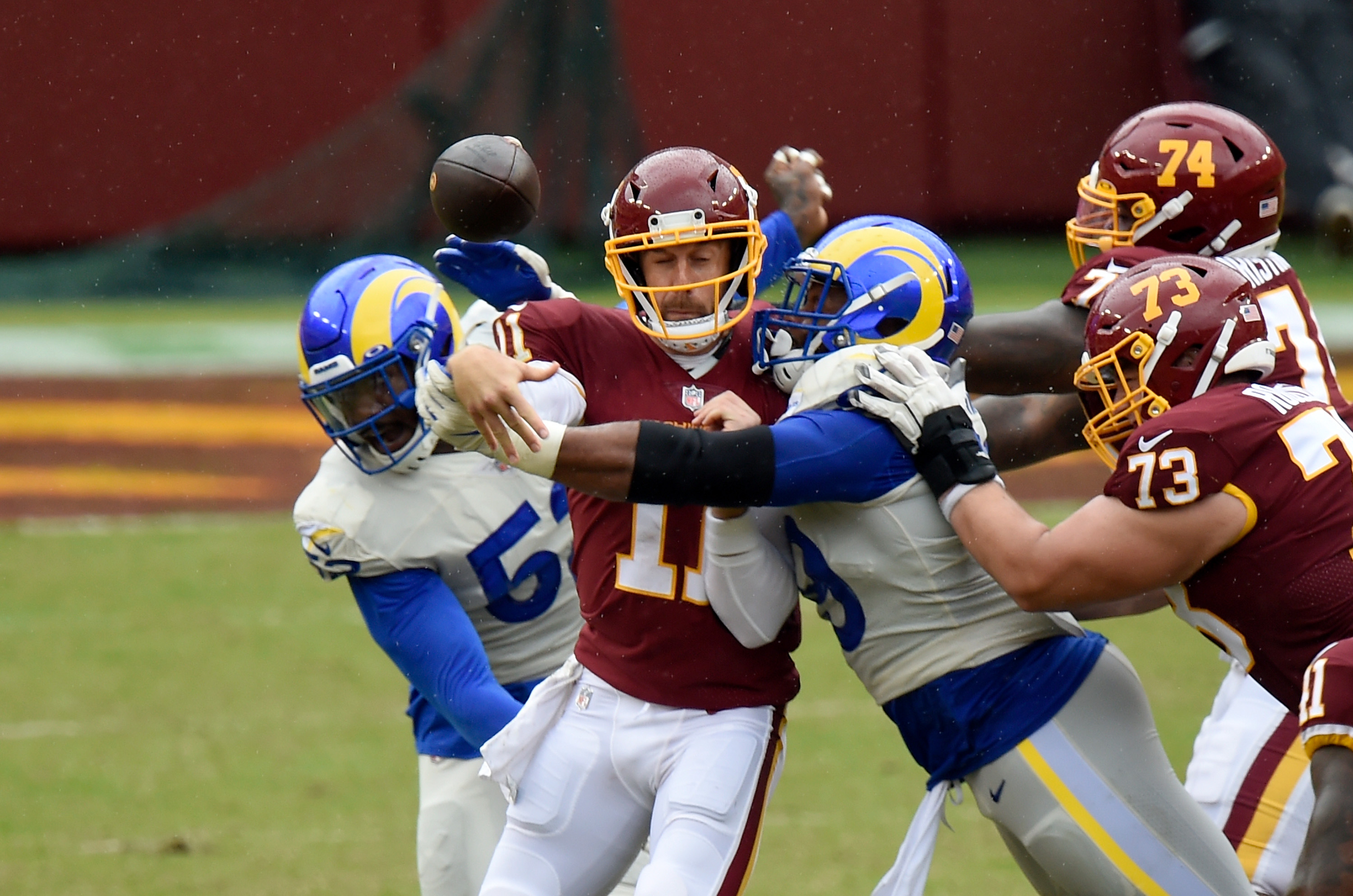 Alex Smith of the Washington Football Team is hit by Aaron Donald of the Rams