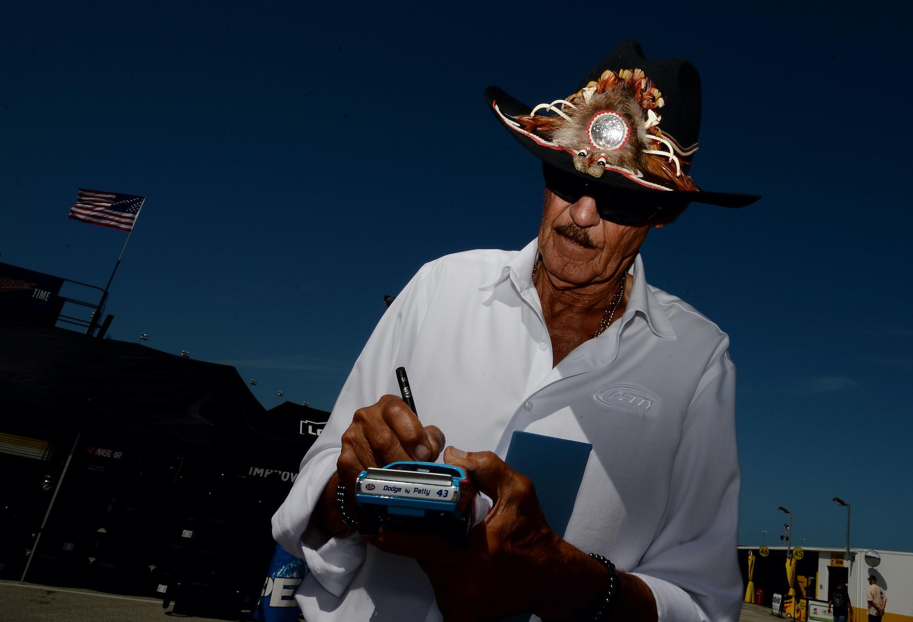 Richard Petty signs an autograph for a NASCAR fan