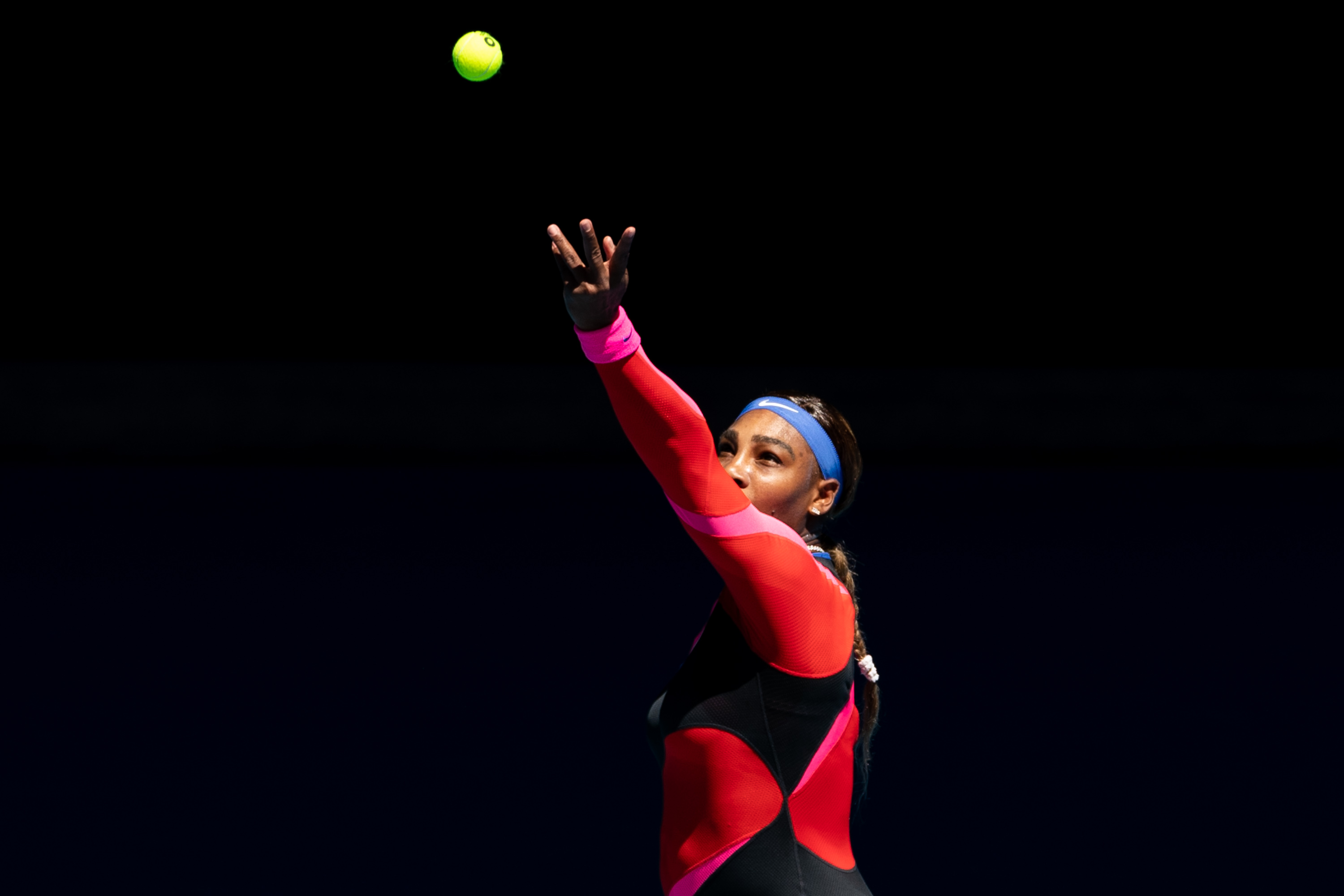 Serena Williams tossing the ball up for a serve during a tennis match