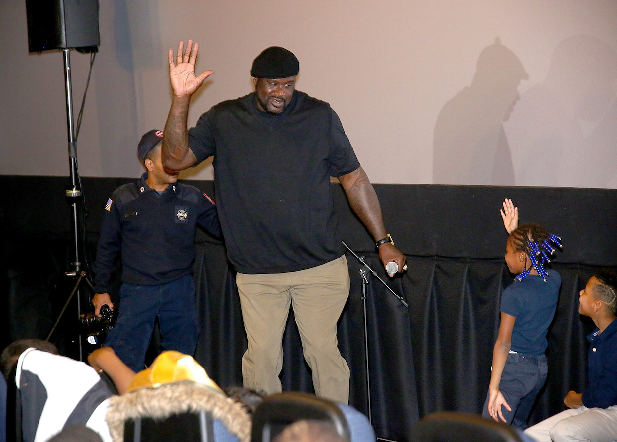 Shaquille O'Neal high fives a young girl