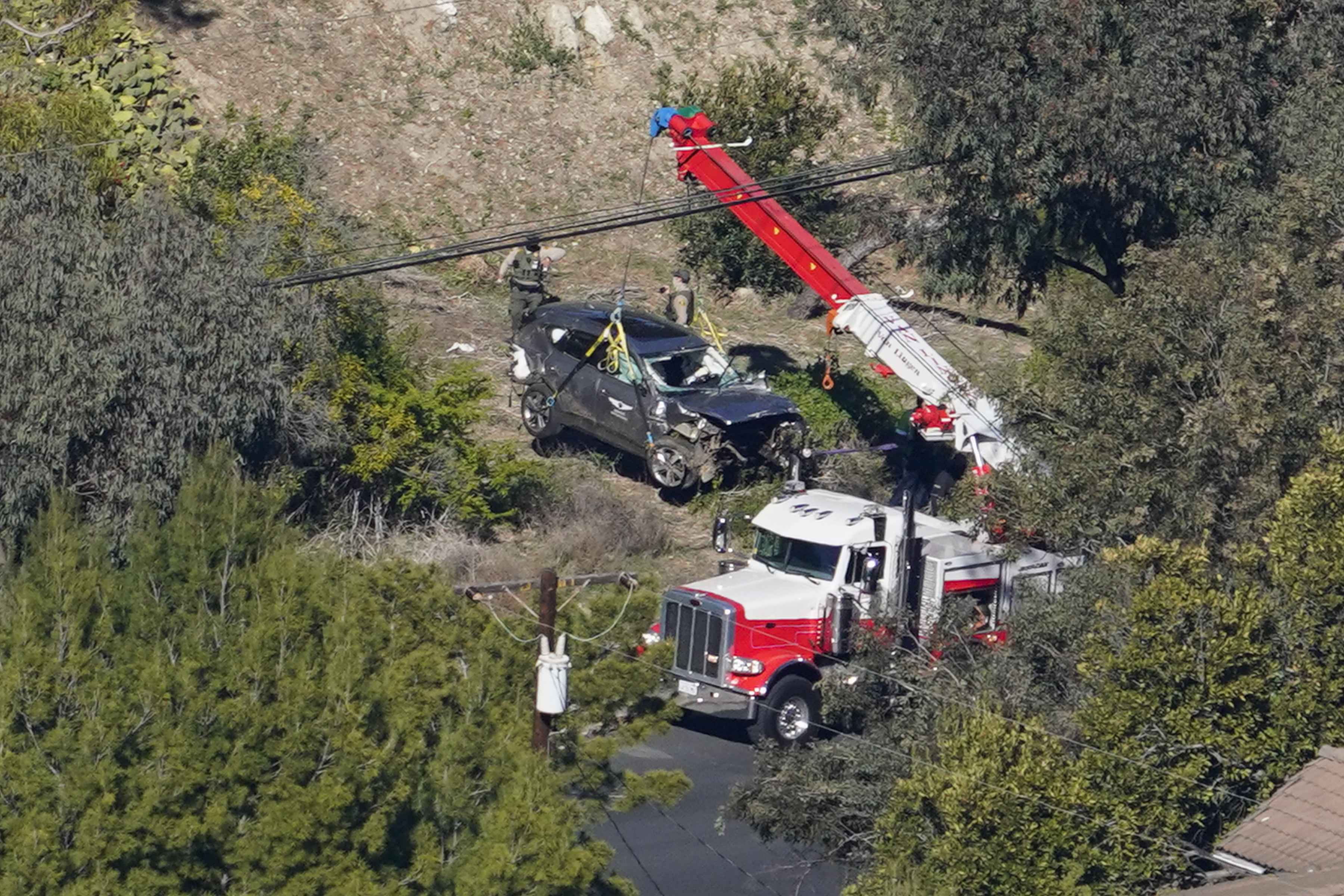 Workers move a vehicle after a rollover accident involving golfer Tiger Woods
