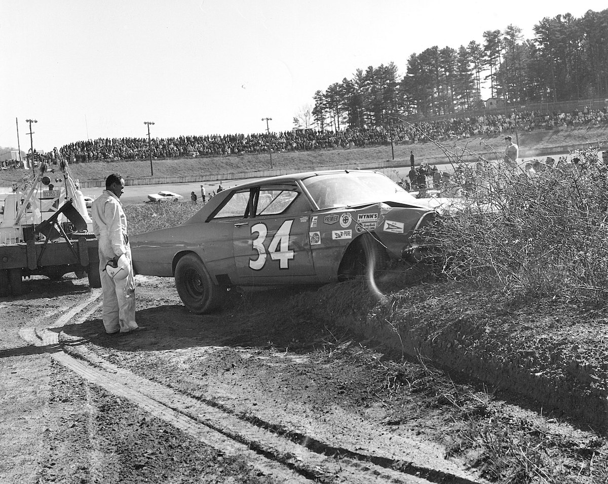 NASCAR driver Wendell Scott assesses the damage to his car after a crash