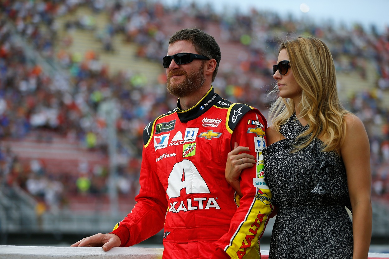 Dale Earnhardt Jr. and his wife Amy Earnhardt stand together before a NASCAR race.