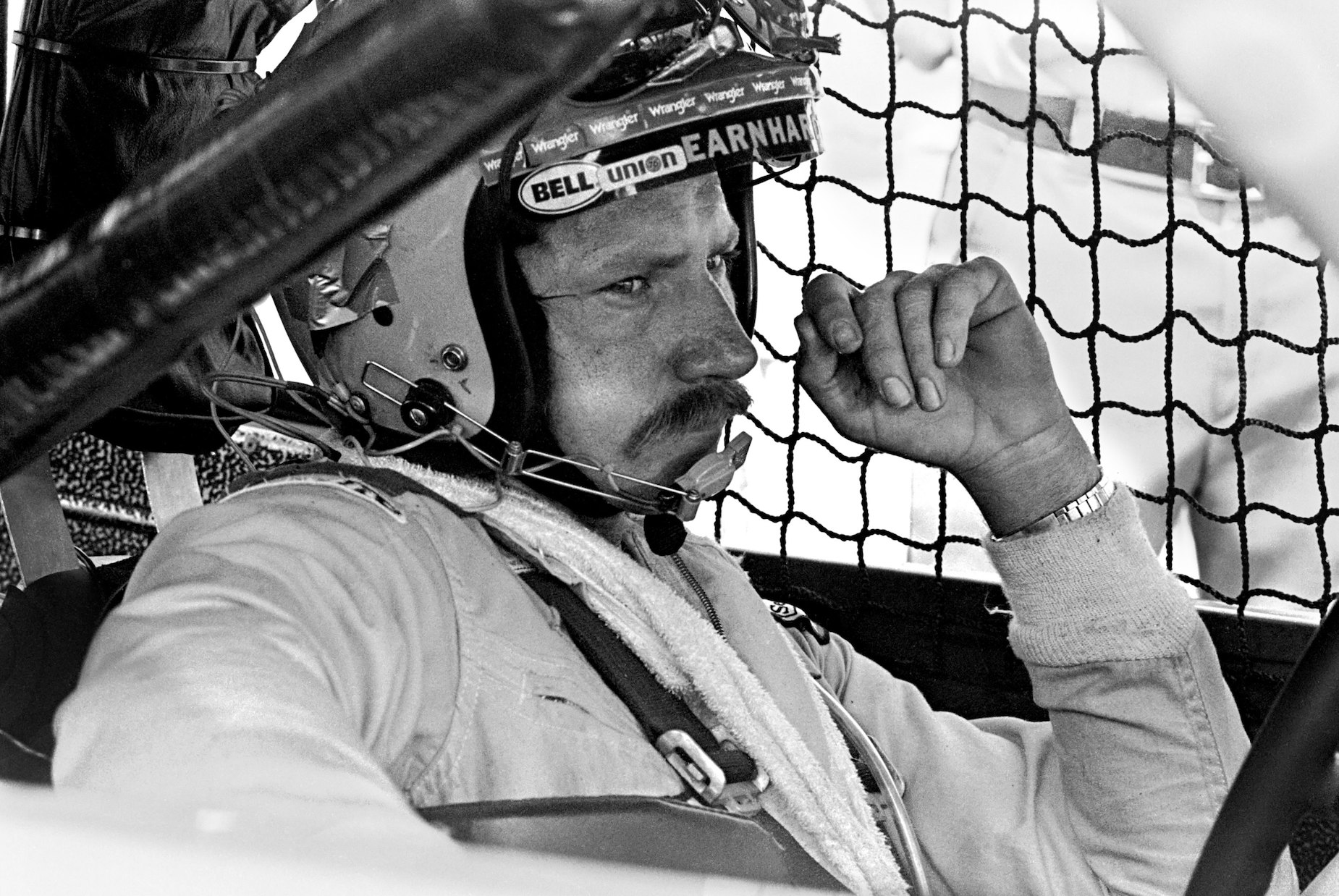 NASCAR driver Dale Earnhardt sits in his car ahead of the 1981 Firecracker 400.