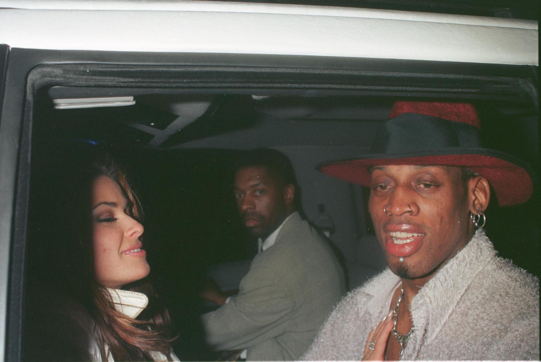 NBA player Dennis Rodman and model Carmen Electra sit in a limousine together in 1999.