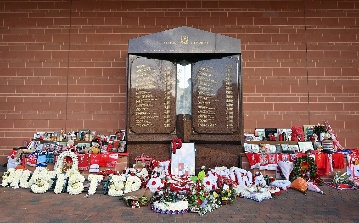 Flowers, shirts, and photos surround the eternal flame of the Hillsborough memorial at Anfield in Liverpool.