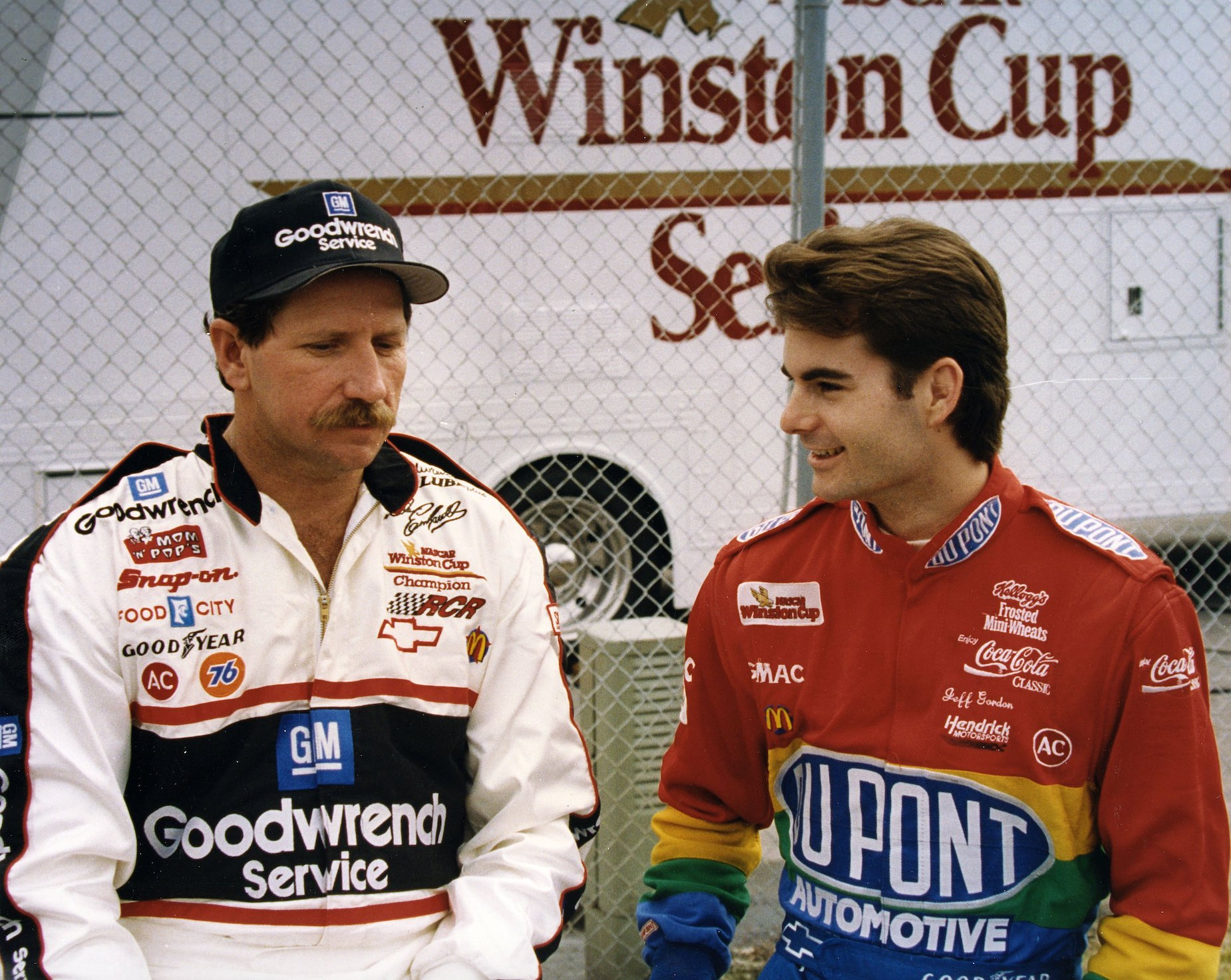 Dale Earnhardt (L) and Jeff Gordon (R) sit together at a race track during the 1990s.
