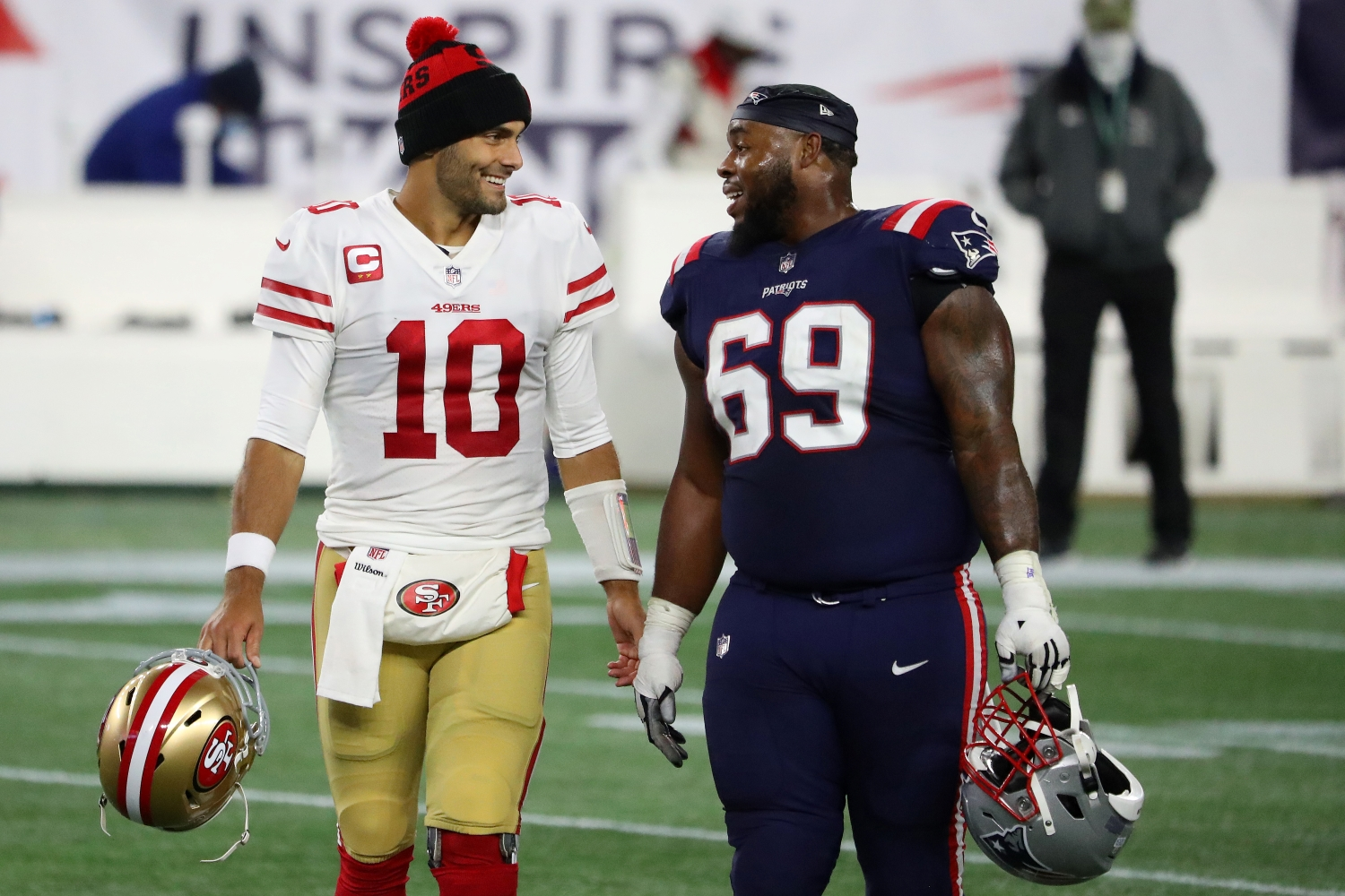 San Francisco 49ers quarterback Jimmy Garoppolo greets former New England Patriots teammate Shaq Mason during a game from the 2020 NFL season.