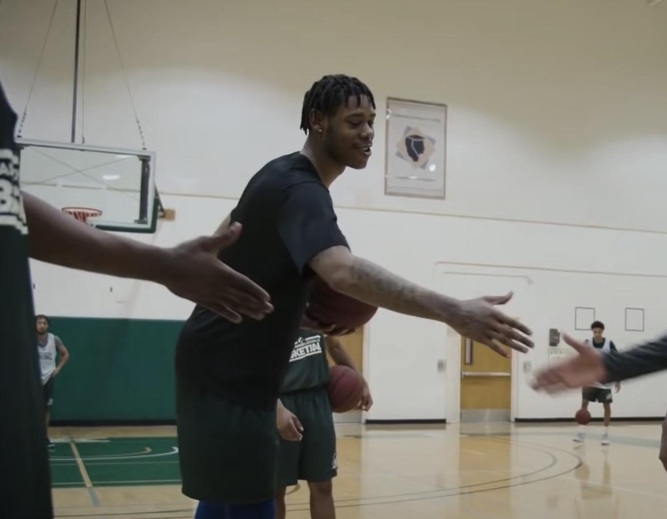Joe Hampton shakes his coach's hand while filming Last Chance U Basketball