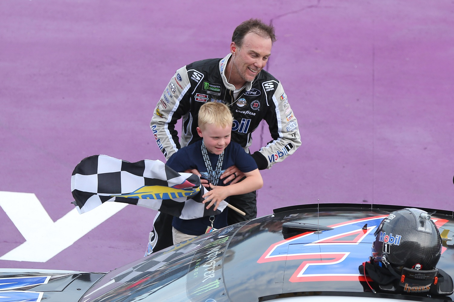 Kevin Harvick helps his son Keelan into the car with the checkered flag after winning the 2019 NASCAR Cup Series Consumers Energy 400 at Michigan International Speedway. | Photo by Matt Sullivan/Getty Images