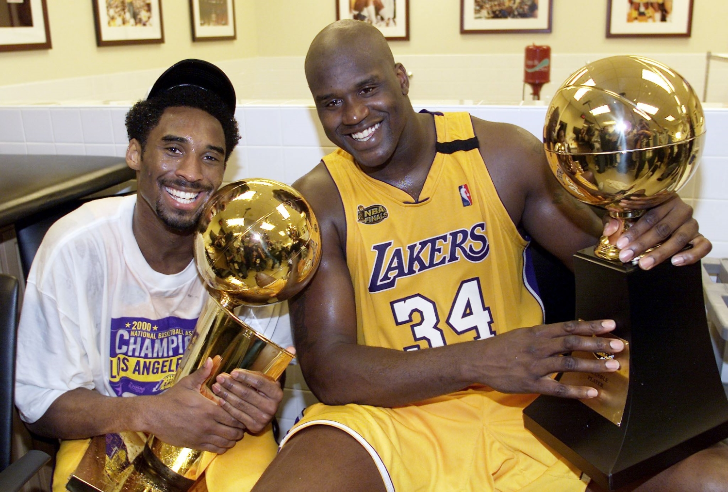 Lakers teammates Kobe Bryant holds the Larry O'Brien Trophy as Shaquille O'Neal holds the NBA Finals MVP trophy.