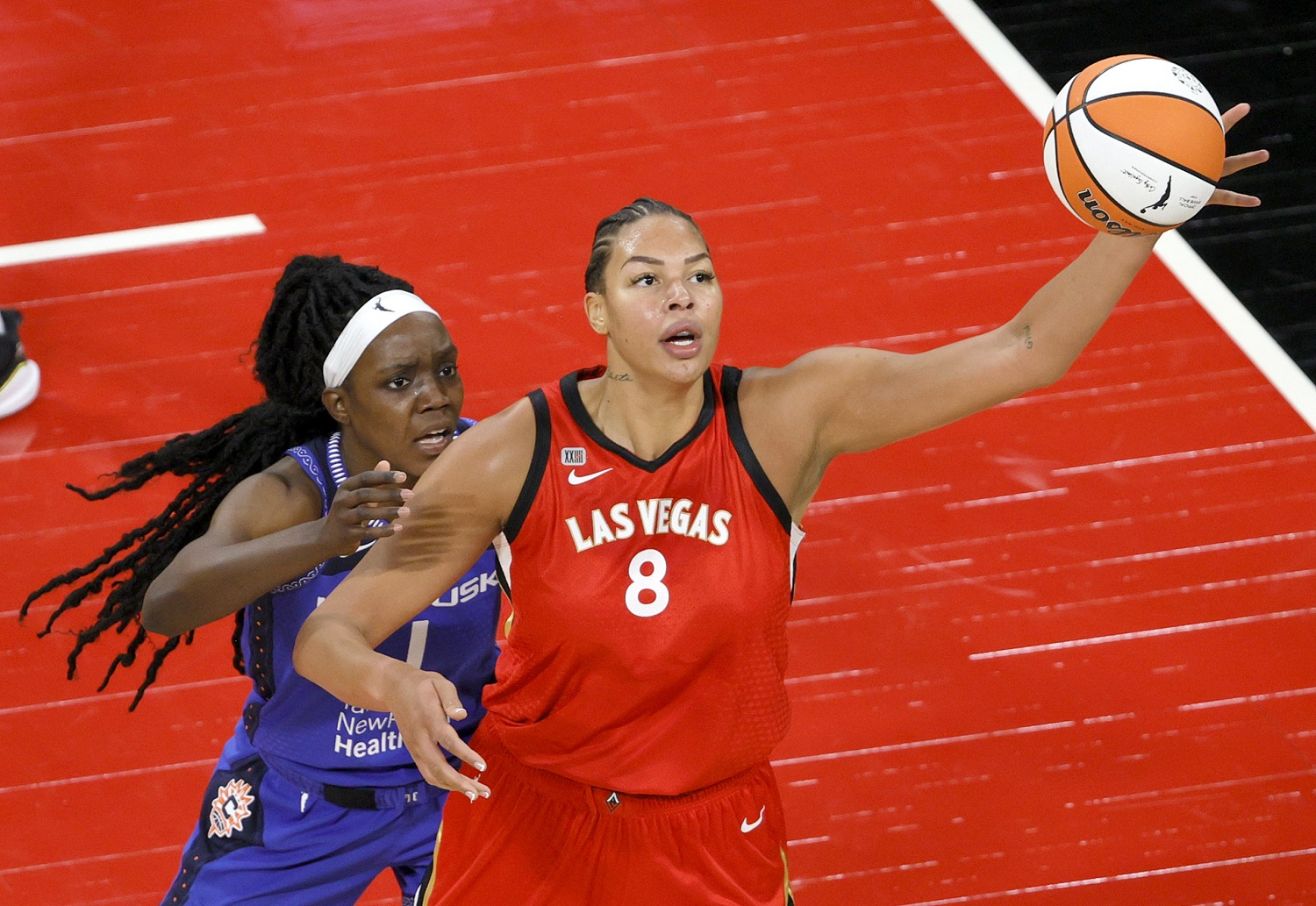 Liz Cambage of the Las Vegas Aces catches a pass under pressure from Beatrice Mompremier of the Connecticut Sun during their game on May 23, 2021 in Las Vegas. | Ethan Miller/Getty Images
