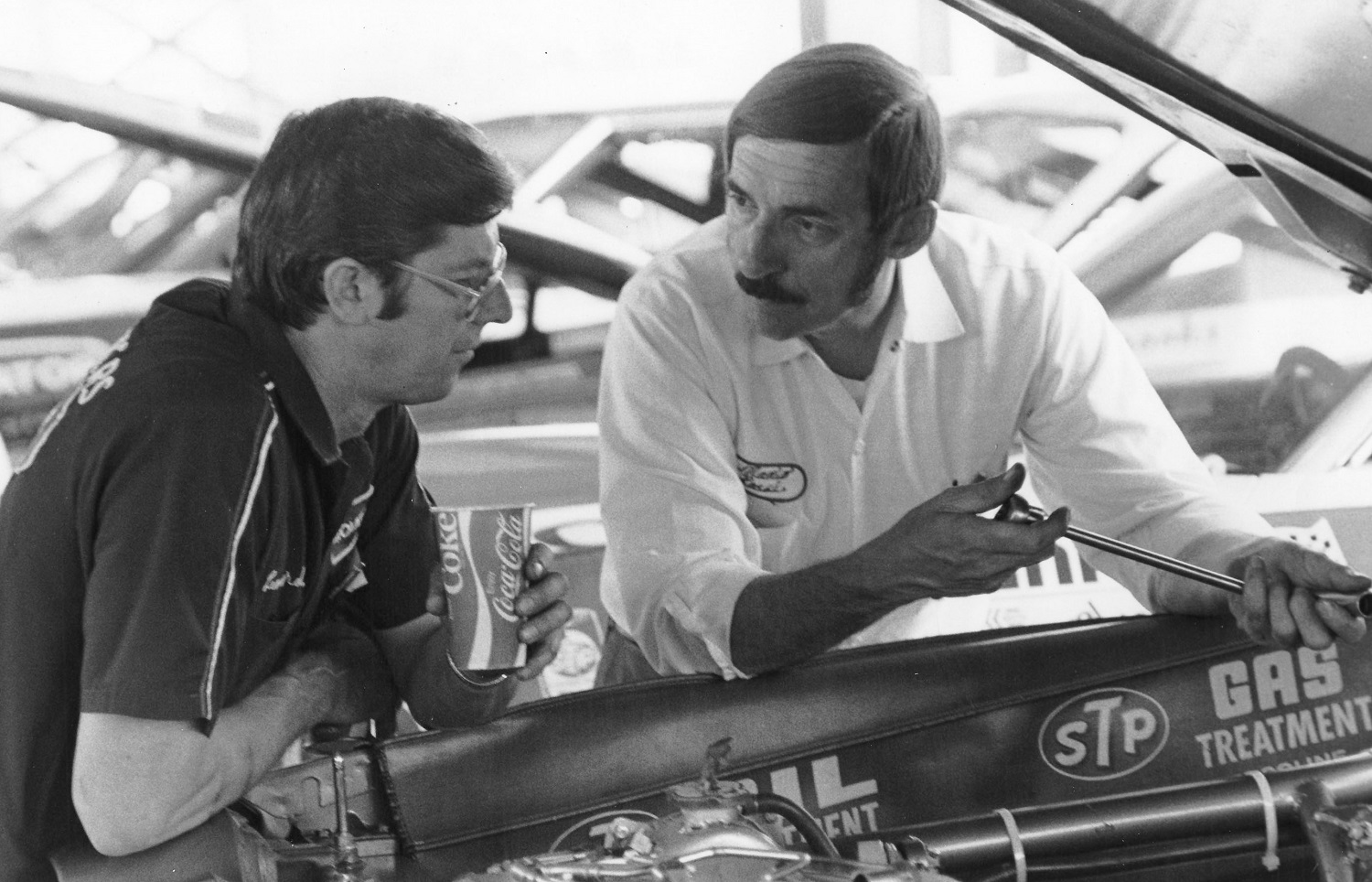 Renowned NASCAR mechanics Leonard Wood and Mario Rossi chat in the garage area at a 1974 NASCAR Cup Series race.   ISC Images & Archives via Getty Images