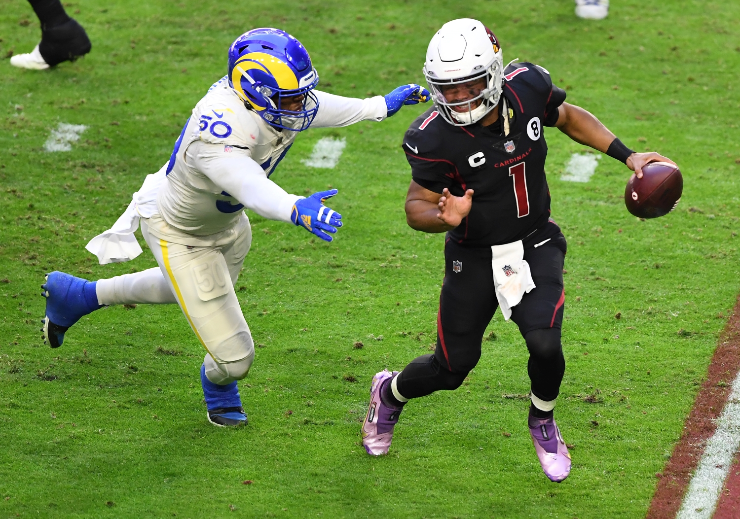 Arizona Cardinals quarterback Kyler Murray tries to avoid getting tackled by an LA Rams defender.