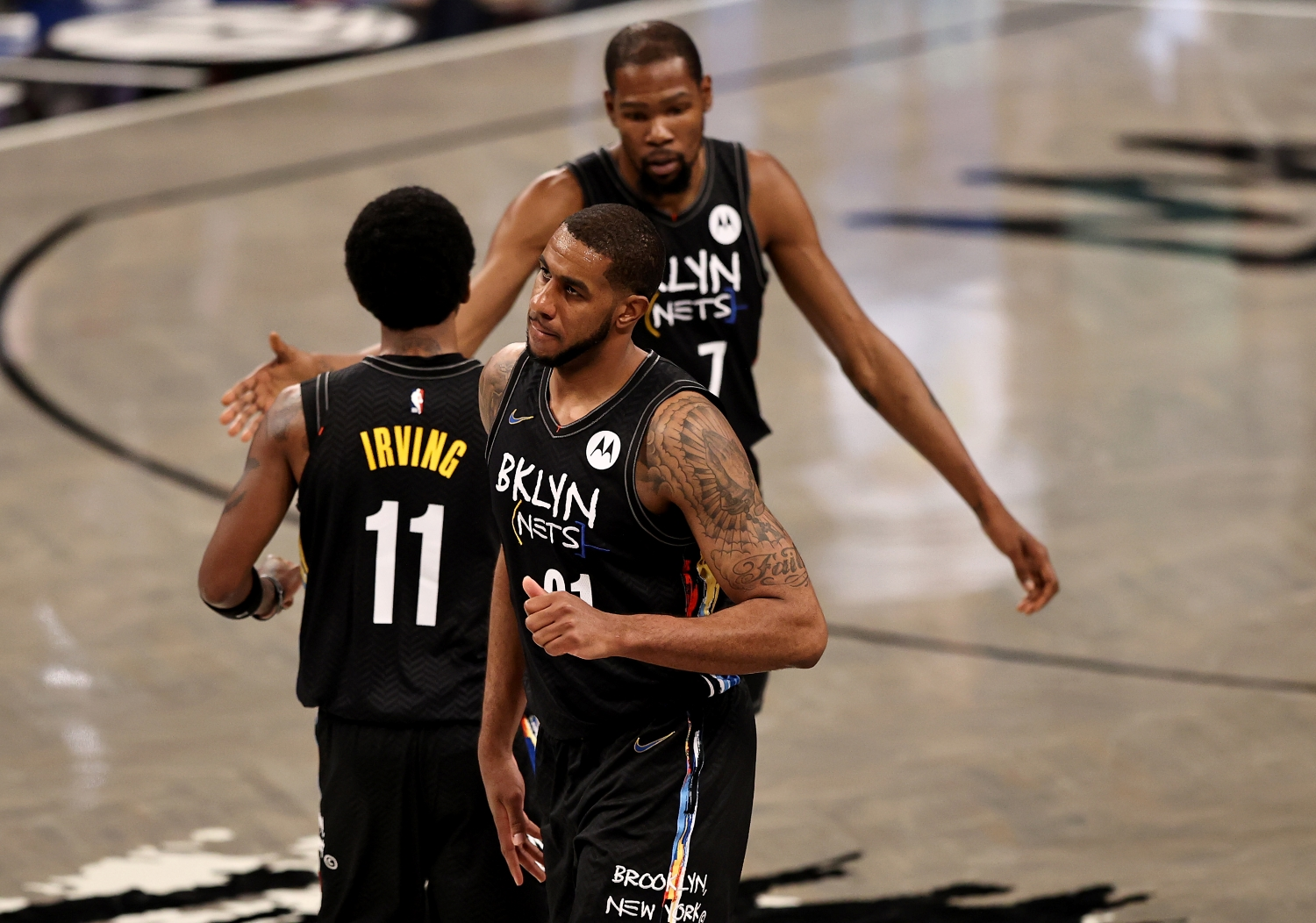 LaMarcus Aldridge walks off the court as Nets teammates Kevin Durant and Kyrie Irving shake hands.