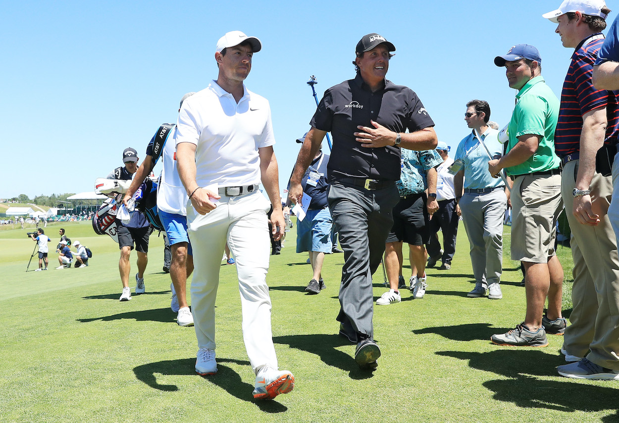 Rory McIlroy and Phil Mickelson walk off the ninth green during the 2018 U.S. Open