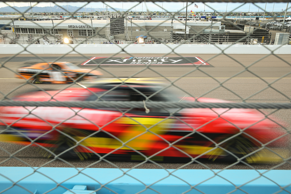 Two blurred NASCAR race cars in front of the Xfinity logo during the Call 811 Before You Dig 200 Nascar Xfinity Series Race on March 13, 2021, at Phoenix ISM Raceway in Phoenix, Arizona
