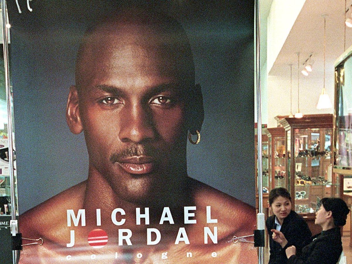 A salesgirl puts up a Michael Jordan cologne poster.